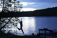 Hortonia, VT, USA - August 22, 2011: Young girl runs down to boat jetty as the sun sets across a lake and clouds from a distant Hurricane Irene approach mid Vermont.