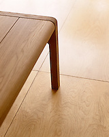Plywood tongue-and-groove flooring panels slot together for easy installation and have been laid in a grid pattern in the kitchen hallway