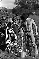 shirtless muscular cowboy in jeans and a cowboy hat on a ranch filling a bucket with water