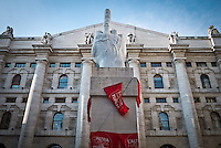 The middle finger sculpure of Maurizio Cattelan coverd of Tsipras red flag during the presentation of Italy's Tsipras List in Piazza Affari (Milan Stock Exchange) , on April 23, 2014. Photo: Adamo Di Loreto/BuenaVista*Photo