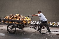 A vendor pushes a cart loaded with bananas.