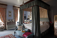 The blue bedroom is furnished with a four-poster bed and a pale blue chaise longue