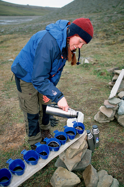 Hiking guide pours hot drinks for her visitors. Bjorndalen. Svalbard