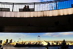 A couple kiss while sitting on a bench overlooking Tokyo Bay, with Rainbow Bridge and the city beyond, in Tokyo's Odaiba district.
