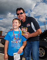 "Sep 2, 2016; Clermont, IN, USA; ""Papa John"" Schnatter, founder of Papa Johns Pizza poses for a photo with a young fan prior to a charity race against NHRA top fuel driver Leah Pritchett qualifying for the US Nationals at Lucas Oil Raceway. Papa John's and DSR put up $10,000 each for Riley's Hospital for Children, adding $20,000 to funds already raised through pizza sales earlier in the day. Mandatory Credit: Mark J. Rebilas-USA TODAY Sports"