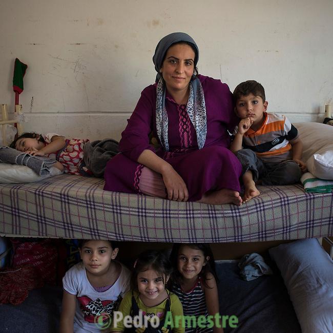 15 septiembre 2015. Ceti-Melilla <br /> Khlam Tami tiene 31 a&ntilde;os y es de Kobani (Siria). Permanece en el Centro de Estancia Temporal de Inmigrantes (Ceti) junto a sus dos hijos, Mohammed, de 4 a&ntilde;os y medio, y Rokach, de un a&ntilde;o y dos meses. Su marido est&aacute; en Nador (Marruecos). La ONG Save the Children exige al Gobierno espa&ntilde;ol que tome un papel activo en la crisis de refugiados y facilite el acceso de estas familias a trav&eacute;s de la expedici&oacute;n de visados humanitarios en el consulado espa&ntilde;ol de Nador. Save the Children ha comprobado adem&aacute;s c&oacute;mo muchas de estas familias se han visto forzadas a separarse porque, en el momento del cierre de la frontera, unos miembros se han quedado en un lado o en el otro. Para poder cruzar el control, las mafias se aprovechan de la desesperaci&oacute;n de los sirios y les ofrecen pasaportes marroqu&iacute;es al precio de 1.000 euros. Diversas familias han explicado a Save the Children c&oacute;mo est&aacute;n endeudadas y han tenido que elegir qui&eacute;n pasa primero de sus miembros a Melilla, dejando a otros en Nador. &copy; Save the Children Handout/PEDRO ARMESTRE - No ventas -No Archivos - Uso editorial solamente - Uso libre solamente para 14 d&iacute;as despu&eacute;s de liberaci&oacute;n. Foto proporcionada por SAVE THE CHILDREN, uso solamente para ilustrar noticias o comentarios sobre los hechos o eventos representados en esta imagen.<br /> Save the Children Handout/ PEDRO ARMESTRE - No sales - No Archives - Editorial Use Only - Free use only for 14 days after release. Photo provided by SAVE THE CHILDREN, distributed handout photo to be used only to illustrate news reporting or commentary on the facts or events depicted in this image.