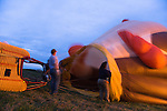 Hot air balloonists  at the Shenandoah Valley Hot Air Balloon Festival at Historic Long Branch in Millwood, Virginia blow air into the balloon &quot;envelope.&quot;  After filling the balloon with air, they will fire a propane burner to heat the air.  Since hot air rises, this will eventually cause the balloon to stand up, then fly up.
