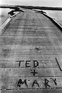July 19th 1969, Chappaquiddick, Edgartown, Martha's Vineyard, Massachusetts,<br /> The Dike wooden bridge on Poucha Pond on Chappaquiddick Island in 1969 with &quot;Ted + Mary&quot; written on it. The site is where aide Mary Jo Kopechne was killed in an car accident when Senator Edward Kennedy was driving.