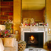 Scarlet leather bindings glow against the pale yellow floral stencils on the walls of this pretty and elegant living room