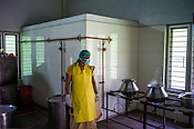 A local worker waits for the herbs to cook to later make medicine at the Pharmacy of the National Research Institute of Panchakarma in Cheruthuruthy in Thissur district of Kerala, India.