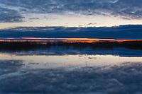 Reflection of clouds on water. Sunset or sunrise. Lake Võrtsjärv at night, Tartu County, Estonia.