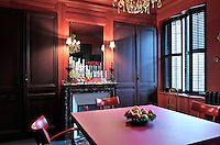 Built-in cupboards painted an aubergine colour, flank a mirror above the marble fireplace in the red dining room