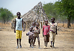 Children walk past the ruins of homes in Leu, a village in the contested Abyei region along the border between Sudan and South Sudan. The village was looted and burned in 2011 when soldiers and militias from the northern Republic of Sudan swept through the area, chasing out more than 100,000 Dinka Ngok residents. A few thousand families have returned to the region since northern combatants withdrew in 2012, yet their life is precarious. In Leu, the Catholic Church rehabilitated a clinic and drilled a well. For political and logistical reasons, the Catholic Church is one of the few organizations willing to openly accompany the people of Abyei during these uncertain times.