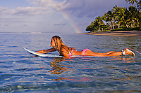 A girl paddles out on a blue surfboard with palm trees and a rainbow in the distance at Lahaina, Maui.