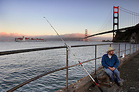 A lone fisherman at Fort Baker dips his line into a San Francisco Bay that has lost many populations of its native aquatic species in the past 150 years. <br /> One potential culprit motors past in the background. Each ship in this busy port carries, on the average a million gallons of water in ballast tanks, for stability in open waters. Large ships often carry 20 million gallons. In the past, water take up in a distant port was released here, devastating the ecosystem. California attempts to regulate the practice but it is still common here and in ports the world over,