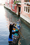 A gondolier in Venice, Italy steers his gondola.