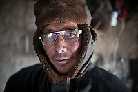 Mamalai, a Kyrgyz man and opium addict, wears brand new glasses, with the sticker still on it..Ech Keli, Er Ali Boi's camp, one of the richest Kyrgyz in the Little Pamir..Trekking with yak caravan through the Little Pamir where the Afghan Kyrgyz community live all year, on the borders of China, Tajikistan and Pakistan.