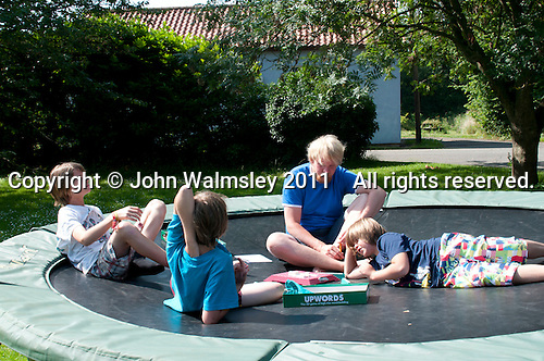 "Philipp Klaus, holding an English class on the trampoline using the ""Upwords"" game, Summerhill School, Leiston, Suffolk. The school was founded by A.S.Neill in 1921 and is run on democratic lines with each person, adult or child, having an equal say.  You don't have to go to lessons if you don't want to but could play all day.  It gets above average GCSE exam results."