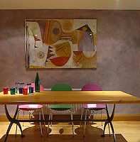 Pink, green and purple chairs are placed along one side of this wooden dining table upon which is a collection of coloured water glasses