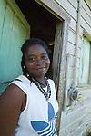 Garifuna craftswoman wearing handmade jewlrey outside her hut in Barranco village, southern Belize