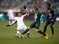 Brian Carroll (7) of the Philadelphia Union tackles the ball away from Lee Nguyen (24) of the New England Revolution during the game at PPL Park in Chester, PA.  The Philadelphia Union defeated the New England Revolution, 1-0.