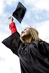 A young woman graduating throwing a graduation cap into the air