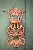 Door knocker design on green painted wooden door in Bourdeilles near Brantome, Northern Dordogne, France