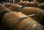 Wine thief and glass on barrels