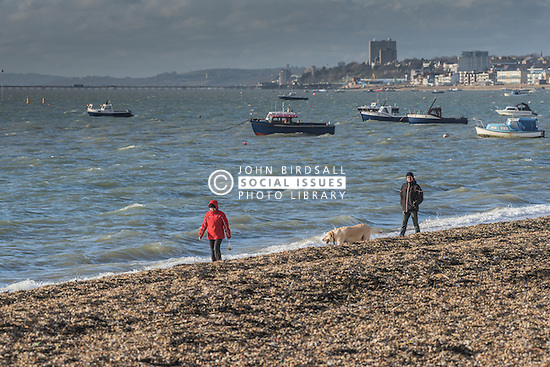 A couple walk their dog along the beach at Thorpe Bay in Southend on Sea, Essex, UK.