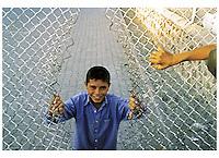 Turchia - Dogubayazit - Ragazzo che sorride aprendo una rete. In primo piano braccio di altro ragazzo