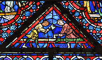 Two men stripping a trunk of its bark, from the donor window of the woodworkers, from the Life of Noah stained glass window, 13th century, in the nave of Chartres cathedral, Eure-et-Loir, France. Chartres cathedral was built 1194-1250 and is a fine example of Gothic architecture. Most of its windows date from 1205-40 although a few earlier 12th century examples are also intact. It was declared a UNESCO World Heritage Site in 1979. Picture by Manuel Cohen