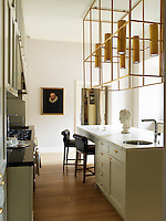Achille Salvagni designed the brass light fixture in this contemporary kitchen; the 1780 Venetian portrait is of a family ancestor, the custom- made cabinetry is painted in Farrow & Ball's Elephant's Breath, and the walls are painted in Skimming Stone.