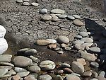 curved, drying creekbed lined with smooth stones that leads to the ocean on the Wsahington Coast