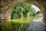 Rural view of English countryside from under a arched bridge along a river at Hungerford, Berkshire.