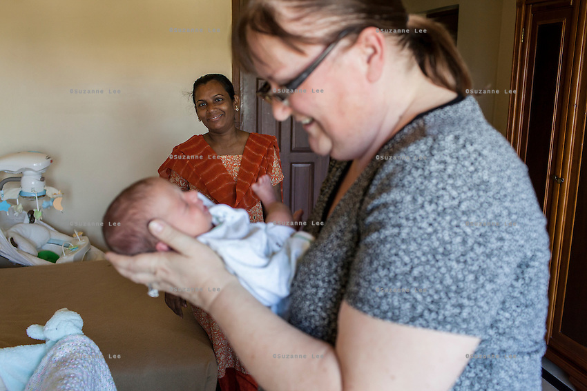 Barbara, from Canada, carries her baby as her surrogate, Idan, comes to breastfeed the baby in her hotel room near the Akanksha Clinic in Anand, Gujarat, India on 11th December 2012. Barbara, from Canada, had come to receive him at his birth from Idan, her surrogate, and is waiting for her husband to come and join her in Anand, while she continues to hire Idan to breastfeed her son so that he gets the best start in life. Idan's husband sends pumped breast milk to Barbara's hotel in the evenings when Idan cannot come personally. Photo by Suzanne Lee / Marie-Claire France