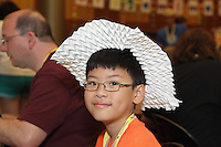 New York, NY, USA - June 23, 2012: Dylan Lee wears a hat made from a tessellated piece of paper. He is attending the annual OrigamiUSA 2012 convention held at Fashion Institute of Technology in New York City. At this international event, experts teach classes of students how to fold various Origami designs.  In the background, attendees are waiting to take classes and learn how to fold various Origami models, from simple to highly complex.