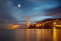 Fog and the moon over the Golden Gate Bridge at sunset, San Francisco, California, USA.