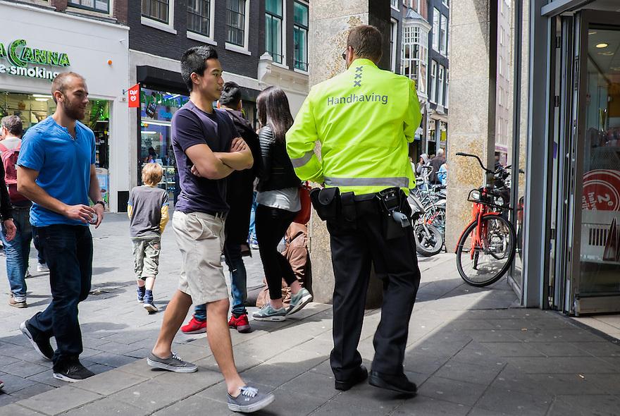 Nederland, Amsterdam, 30 mei 2015<br /> Handhaver bij de ingang van een winkel<br /> Foto: Michiel Wijnbergh