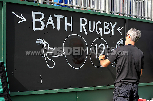 Artist & Illustrator Simon Spilsbury keeps the scoreboard up to date. Pre-season friendly match, between Bath Rugby and the Scarlets on August 16, 2014 at the Recreation Ground in Bath, England. Photo by: Patrick Khachfe / Onside Images
