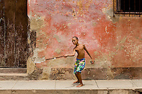 Boy playing stickball in the street