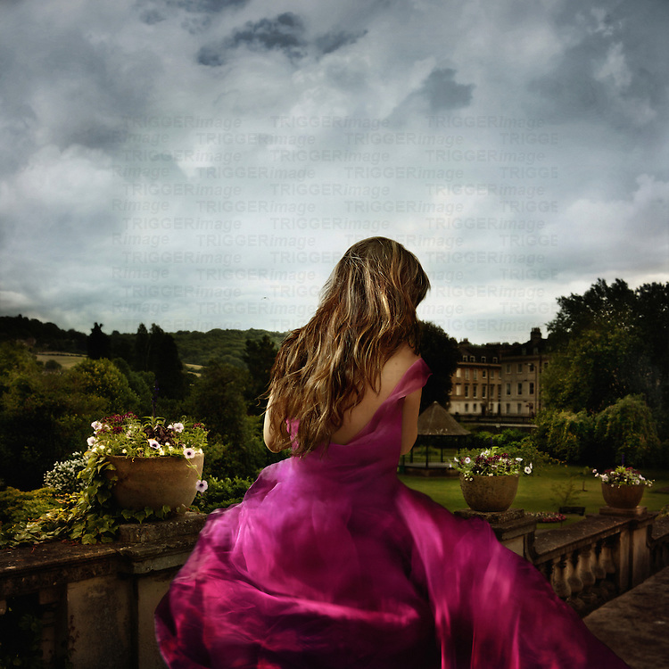 Rear view of a young woman with long hair wearing a pink silk party dress outdoors in the gardens of a large english house under cloudy skies