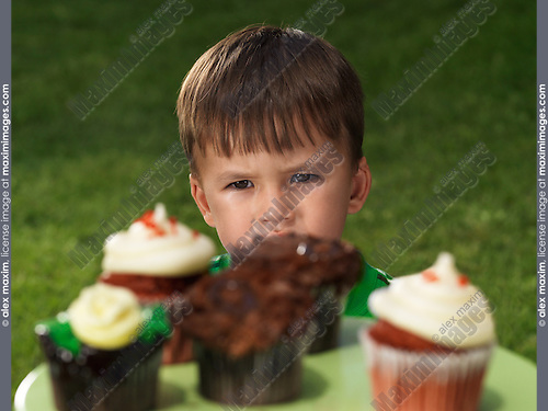 Two year old boy looking at a stand with sweet cupcakes