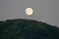 Moon rising over Mountain top.