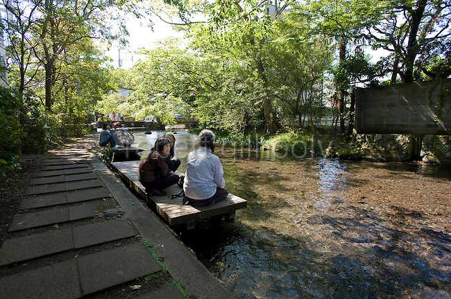 Residents enjoys a chat by the Genbe River  in Mishima, Shizuoka Prefecture Japan on 02 Oct. 2012.  Photographer: Robert Gilhooly