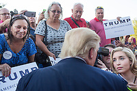 Real estate mogul and Republican presidential candidate Donald Trump speaks with a television reporter after speaking to supporters at a rally at the Weirs Beach Community Center in Laconia, New Hampshire.