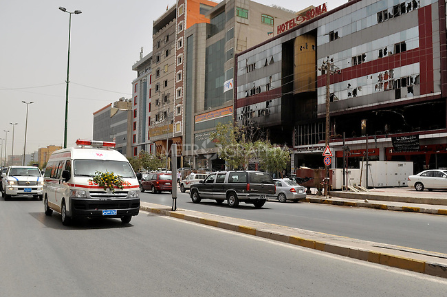 SULAIMANIYAH, IRAQ: Ambulances pass in front of the Soma Hotel carrying the remains of the foreigners killed in a hotel fire.<br /> <br /> On July 15, 2010 a fire in the Soma Hotel killed around 40 people including women, children and internationals from the US, Britain, Canada, Australia, Venezuela, Lebanon, South Africa, Bangladesh, the Philippines, Sri Lanka, and Cambodia..Photo by Aram Karim/ Metrography