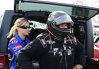 Sept. 28, 2012; Madison, IL, USA: NHRA funny car driver Terry Haddock is helped with safety gear by wife Jenna Haddock during qualifying for the Midwest Nationals at Gateway Motorsports Park. Mandatory Credit: Mark J. Rebilas-