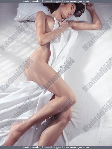 Beautiful young woman sleeping naked in bed covering with white sheets