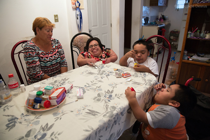 From left to right: Brenda Eduardo Torres, 32 - Joaquin Eduardo Torres Gil, 14 and Alfredo Ivan Torres Gil, 18 - are eating a yogurt with their mother Joaquina at their home in Mexico City, Mexico on February 16, 2017. The three siblings have been diagnosed with Morquio syndrome. Morquio syndrome is a rare inherited birth defect that is estimated to occur in one of every 200,000 births. The disease may not be visible at birth; symptoms usually begin between ages 1 and 3. Morquio syndrome is a progressive disease, meaning symptoms get worse as a child grows. Photo credit: Bénédicte Desrus