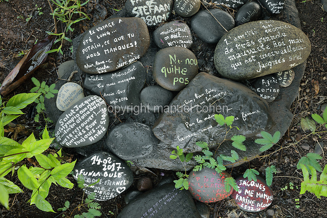 Stones with messages painted on them, at the tomb of the Belgian singer Jacques Brel, 1929-78, in Calvary Cemetery, near Atuona, on the island of Hiva Oa, in the Marquesas Islands, French Polynesia. The tomb features a relief portrait of Brel with his partner, Maddly Bamy, a Guadeloupe born French actress and singer. Picture by Manuel Cohen